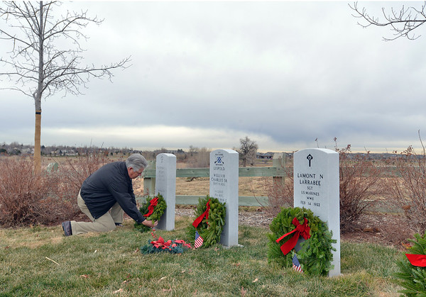 John O'Hayre places a holiday wreath on the grave of a military veteran on Saturday at the Broomfield County Commons Cemetery for the Wreaths Across America. The Broomfield Rotary Club sponsored event placed wreaths on the graves of veterans at three cemeteries simultaneously.<br /> December 14, 2012<br /> staff photo/ David R. Jennings