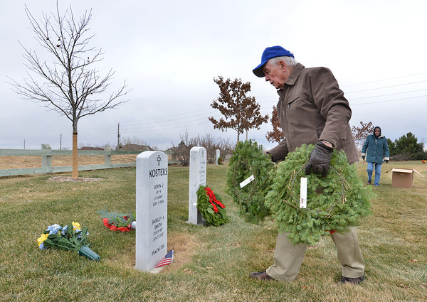 Lew Moir, retired US Air Force colonel, places holiday wreaths on the graves of military veterans on Saturday at the Broomfield County Commons Cemetery for the Wreaths Across America. The Broomfield Rotary Club sponsored event placed wreaths on the graves of veterans at three cemeteries simultaneously.<br /> December 15, 2012<br /> staff photo/ David R. Jennings