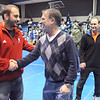 Former wrestler Chad Johnson, left, greets Mark Schmidt, Broomfield High's head wrestling coach, after a ceremony honoring Schmidt's 32 year career on Thursday.  Asstistant coach Craig Johnson and Chad's father is at right.<br /> <br /> January 28, 2010<br /> Staff photo/David R. Jennings