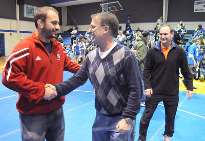 Former wrestler Chad Johnson, left, greets Mark Schmidt, Broomfield High's head wrestling coach, after a ceremony honoring Schmidt's 32 year career on Thursday.  Asstistant coach Craig Johnson and Chad's father is at right.  January 28, 2010 Staff photo/David R. Jennings