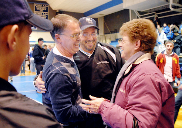 Mark Schmidt, second left, Broomfield High's wrestling coach, greets his first state placer Todd Harrington and Todd's mother Barb Harrington after Schmidt's last home wrestling match on Thursday. After 32 years Schmidt is retiring from coaching and teaching this year. <br /> <br /> January 28, 2010<br /> Staff photo/David R. Jennings