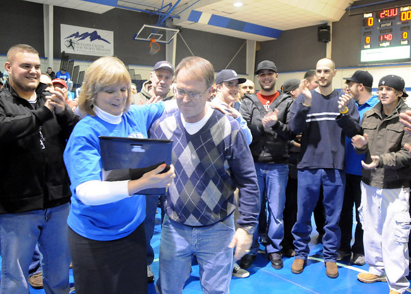 Surrounded by former players and assistant coaches, Mark Schmidt, Broomfield High's wrestling coach is given a plaque by principal Ginger Ramsey during a ceremony celebrating Schmidt's career at his last home wrestling match on Thursday. After 32 years Schmidt is retiring from coaching and teaching this year. <br /> <br /> January 28, 2010<br /> Staff photo/David R. Jennings