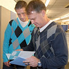Mark Schmidt, right, Broomfield High's wrestling coach, with his son and asstitant coach Matt Schmidt reads a card from his players before  last home wrestling match on Thursday. After 32 years Mark Schmidt is retiring from coaching and teaching this year. <br /> <br /> January 28, 2010<br /> Staff photo/David R. Jennings