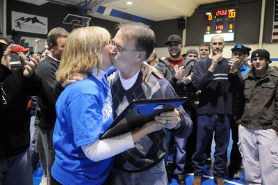 Surrounded by former players and assistant coaches, Mark Schmidt, Broomfield High's wrestling coach, accepts a plaque from principal Ginger Ramsey during a ceremony celebrating his career at his last home wrestling match on Thursday. After 32 years Schmidt is retiring from coaching and teaching this year.   January 28, 2010 Staff photo/David R. Jennings