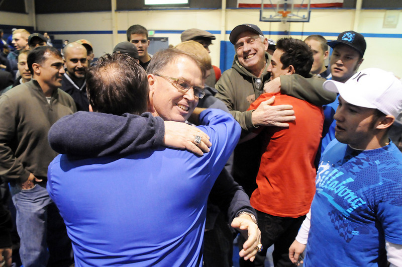 Surrounded by former players and assistant coaches, Mark Schmidt, Broomfield High's wrestling coach, hugs his former assitant coach Craig Walker during a ceremony celebrating his career at his last home wrestling match on Thursday. After 32 years Schmidt is retiring from coaching and teaching this year. <br /> <br /> January 28, 2010<br /> Staff photo/David R. Jennings