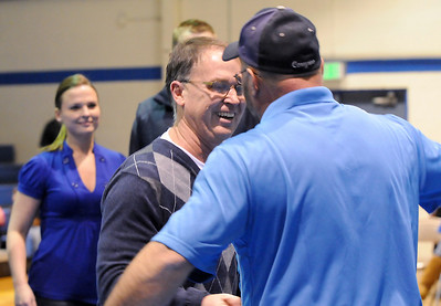 Mark Schmidt, left,  Broomfield High's wrestling coach, greets his first state placer Todd Harrington from Ovid, Colorado, during a ceremony celebrating his career at his last home wrestling match on Thursday. After 32 years Schmidt is retiring from coaching and teaching this year.   January 28, 2010 Staff photo/David R. Jennings