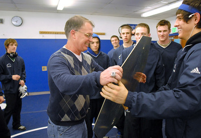 Mark Schmidt, center, Broomfield High's wrestling coach, accepts a gift from the team before his last home wrestling match on Thursday. After 32 years Schmidt is retiring from coaching and teaching this year.    January 28, 2010 Staff photo/David R. Jennings