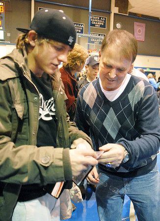 Former Broomfield wrestler John Ness shows pictures to Mark Schmidt, Broomfield High's wrestling coach before Schmidt's last  home wrestling match on Thursday.  <br /> <br /> January 28, 2010<br /> Staff photo/David R. Jennings