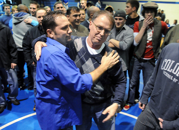 Surrounded by former players and assistant coaches, Mark Schmidt, Broomfield High's wrestling coach, hugs his former assitant coach Craig Walker, left,  during a ceremony celebrating Schmidt's career at his last home wrestling match on Thursday. After 32 years Schmidt is retiring from coaching and teaching this year. <br /> <br /> January 28, 2010<br /> Staff photo/David R. Jennings
