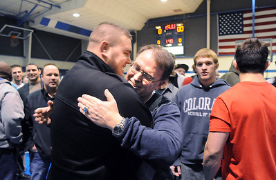 Surrounded by former players and assistant coaches, Mark Schmidt, Broomfield High's wrestling coach, hugs Vinny Pallone, left,  during a ceremony celebrating his career at his last home wrestling match on Thursday. After 32 years Schmidt is retiring from coaching and teaching this year.   January 28, 2010 Staff photo/David R. Jennings