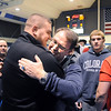Surrounded by former players and assistant coaches, Mark Schmidt, Broomfield High's wrestling coach, hugs Vinny Pallone, left,  during a ceremony celebrating his career at his last home wrestling match on Thursday. After 32 years Schmidt is retiring from coaching and teaching this year. <br /> <br /> January 28, 2010<br /> Staff photo/David R. Jennings
