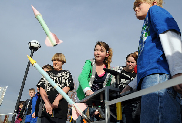 Megan Abel, 13, center, launches paper rockets with her brother Steven, right, 9, using 60 psi of air from a bicycle pump platform made by Lockheed Martin employees during the Rocket Works program Saturday at Mamie Doud Eisenhower Public Library. Thirty students attended the program.<br /> <br /> February 6, 2010<br /> Staff photo/David R. Jennings
