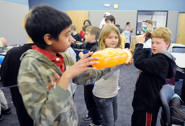Karthik Subramaniam, 11, left, with Kendall Monley, 10, and Aidan Svensk, 9, prepare to launch a balloon rocket guided by a string during the Rocket Works program Saturday at Mamie Doud Eisenhower Public Library.<br /> <br /> February 6, 2010<br /> Staff photo/David R. Jennings