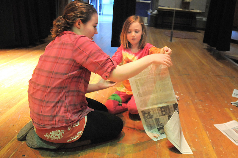 Thespian Tristine Henderson, left, helps Anna Schoenfeld, 8, make a newspaper puppet during the Young Actors Theatre Camp by the Broomfield High School Thespians at the school on Tuesday. <br /> December 29, 2010<br /> staff photo/David R. Jennings