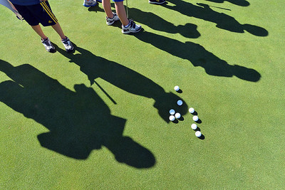 The shadows of young golfers in the 5 - 7 year olld group wait to putt during Thursday's Youth Golf Camp at Eagle Trace Golf Course.  July 19, 2012 staff photo/ David R. Jennings