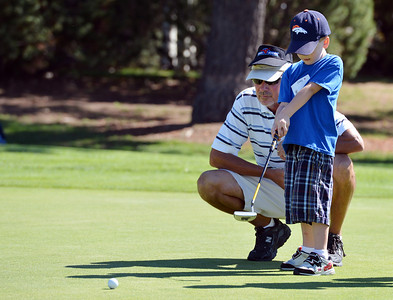 Instructor Dave Sisson, left, watches the putt by Joey Kolodgy, 4, during Thursday's Youth Golf Camp at Eagle Trace Golf Course.  July 19, 2012 staff photo/ David R. Jennings