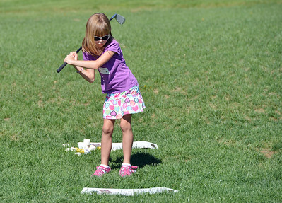 Kathleen Brening takes a practice swing during Thursday's  5 - 7 year old group of the Youth Golf Camp at Eagle Trace Golf Course.  July 19, 2012 staff photo/ David R. Jennings