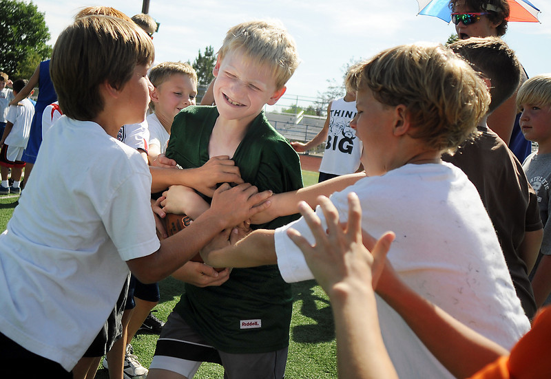 Aedan Collins, 8, center, runs through a gauntlet for running back practice during Broomfield High School Football Camp at Elizabeth Kennedy Stadium on Tuesday.<br /> July 27, 2010<br /> Staff photo/ David R. Jennings