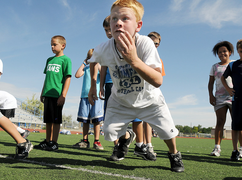 Hayden VanDePol, 10, runs off the line to block during Broomfield High School Football Camp at Elizabeth Kennedy Stadium on Tuesday.<br /> July 27, 2010<br /> Staff photo/ David R. Jennings