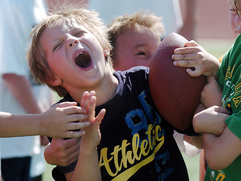 Keenan Leonard, 8, runs through a gauntlet of fellow players trying to take the ball from him during Broomfield High School Football Camp at Elizabeth Kennedy Stadium on Tuesday.<br /> July 27, 2010<br /> Staff photo/ David R. Jennings