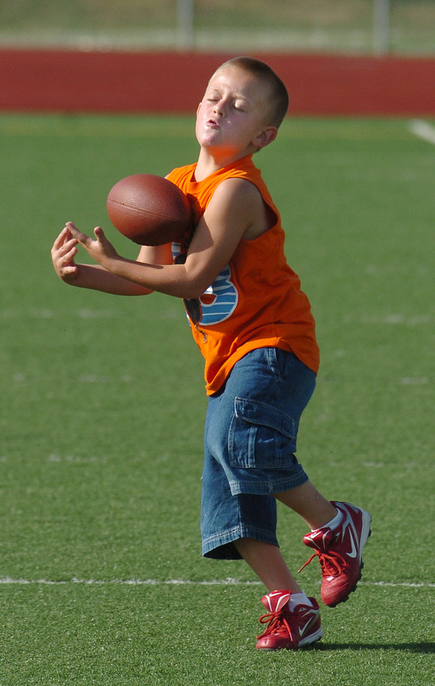 Derrick Geist, 7, tries to catch the ball during Broomfield High School Football Camp at Elizabeth Kennedy Stadium on Tuesday.<br /> July 27, 2010<br /> Staff photo/ David R. Jennings
