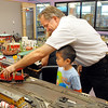 Larry Price puts a model train on the track while Samuel Law, 5, watches during the Youth in Model Railroading exhibit at Mamie Doud Eisenhower Public Library's Children's Library on Saturday.<br /> <br /> Sept. 26, 2009<br /> Staff photo/David R. Jennings