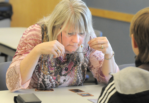 Sheryl Baltzer, 50, studies the cards while playing Noah Parko, 11,  during the Yu-Gi-Oh! tournament at Mamie Doud Eisenhower Public Library on Tuesday.<br /> November 23, 2010<br /> staff photo/David R. Jennings