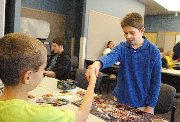 Ethan Cranston, 9, left, and Jonathan Guener, 12, shake hands after playing a game during the Yu-Gi-Oh! tournament at Mamie Doud Eisenhower Public Library on Tuesday.<br /> November 23, 2010<br /> staff photo/David R. Jennings