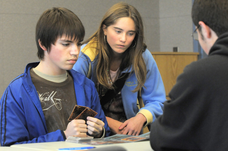 Axl Raditz, 14, left, plays Josh Gruener, 16, right, while Audrey Faulkenburg, 14, watches the game during the Yu-Gi-Oh! tournament at Mamie Doud Eisenhower Public Library on Tuesday.<br /> November 23, 2010<br /> staff photo/David R. Jennings