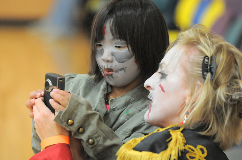 Maggie Rieken, 6, left, gets some pointers on the use of a camera from her mother , Julie, to take pictures of Michael Jackson's Thriller dance at the Paul Derda Recreation Center on Saturday as a fundriaser for A Precious Child.<br /> October 29, 2011<br /> staff photo/ David R. Jennings
