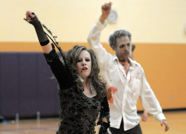 "Janell Durnen, left, and Ean Biggs dance to Michael Jackson's Thriller with 100 other ""zombies"" at the Paul Derda Recreation Center on Saturday as a fundraiser for A Precious Child. <br /> October 29, 2011<br /> staff photo/ David R. Jennings"