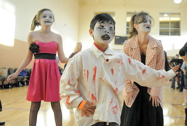 Li Zhi Rieken, 8, front, dances with Emma Howard, 13, left, and her mother, Christy, to Michael Jackson's Thriller at the Paul Derda Recreation Center on Saturday as a fundriaser for A Precious Child.<br /> October 29, 2011<br /> staff photo/ David R. Jennings