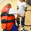 Leominster Police Officer Mike Salovardos helps Jeffrey Arsenault, 8, suit up for the RAD Training at the Leominster Boys & Girls Club on Friday afternoon. SENTINEL & ENTERPRISE / Ashley Green