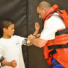 Leominster Police Officer Mike Salovardos helps Tyson Trimel, 8, suit up for the RAD Training at the Leominster Boys & Girls Club on Friday afternoon. SENTINEL & ENTERPRISE / Ashley Green