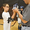 Leominster Police Officer Oswaldo Ramos helps Anastasia Arsenault, 10, suit up for the RAD Training at the Leominster Boys & Girls Club on Friday afternoon. SENTINEL & ENTERPRISE / Ashley Green