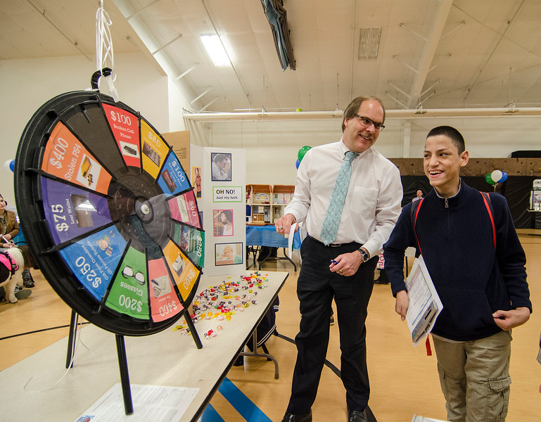 """Kevin Noyes, of People's United Bank, shares a laugh with Anthony Calderon as he spins a """"broken cell phone"""" to pay for during the Reality Fair at the Leominster Boys and Girls Club on Wednesday afternoon. SENTINEL & ENTERPRISE / Ashley Green"""