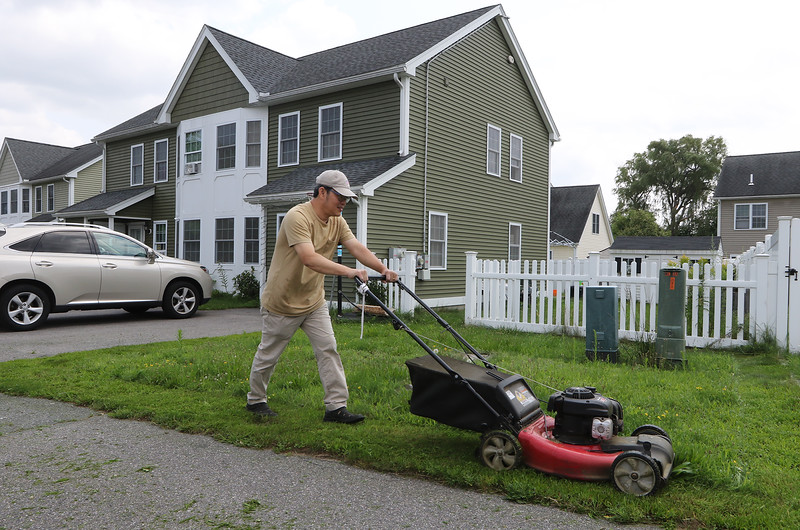 JUly 21, 2021 -- River's Edge on the Concord, in Lowell, where construction of single family and duplex houses began in 2006. Kim Srun, a four-year resident of Murray Lane, mows his lawn.  SUN/Julia Malakie