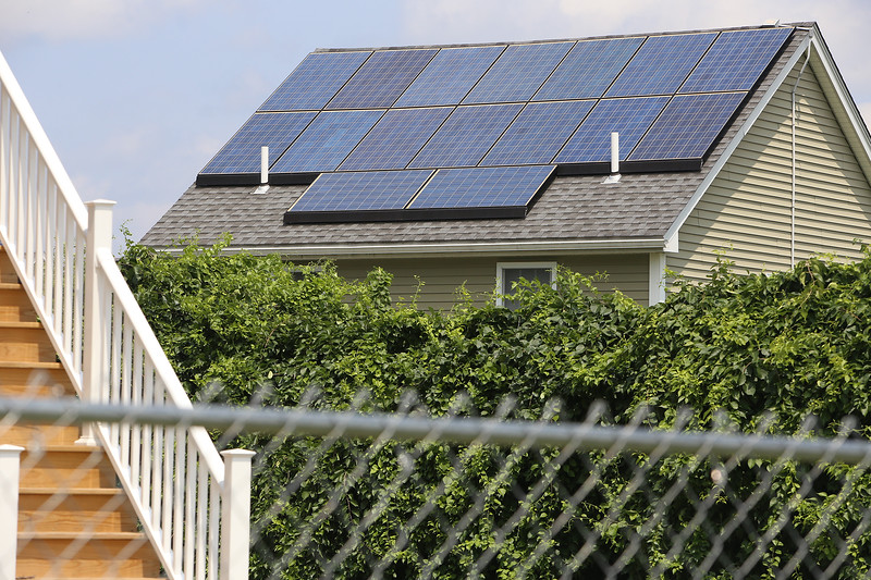 JUly 21, 2021 -- River's Edge on the Concord, in Lowell, where construction of single family and duplex houses began in 2006. Solar panels on a roof. The stairs in the foreground are new construction that appears to be a separate development, Mill City Crossing, which is next to River's Edge on Gorham Street.  SUN/Julia Malakie