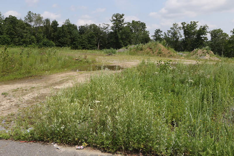 JUly 21, 2021 -- River's Edge on the Concord, in Lowell, where construction of single family and duplex houses began in 2006. Mounds of earth at the far end of the south branch of Adie Way.  SUN/Julia Malakie