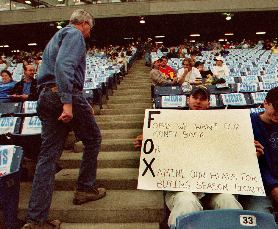 """. A passerby checks out Joseph  Okray\'s sign that reads \""""Ford we want our mney back Or Xamine our heads for buying season tickets\"""" during the Detroit Lions 29-27 loss to the Green Bay Packers Thursday at the Pontiac Silverdome.  The letters of each part of the sign spell out FOX, it was Okray\'s attempt to get his face on TV."""