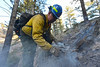 A firefighter from Boulder Mountain Fire breakes open a snag to get to the fire smoldering inside on Tuesday. The fierce winds over the weekend caused a series of spot fires, as well as the big eastward puh from the Fern Lake Fire.