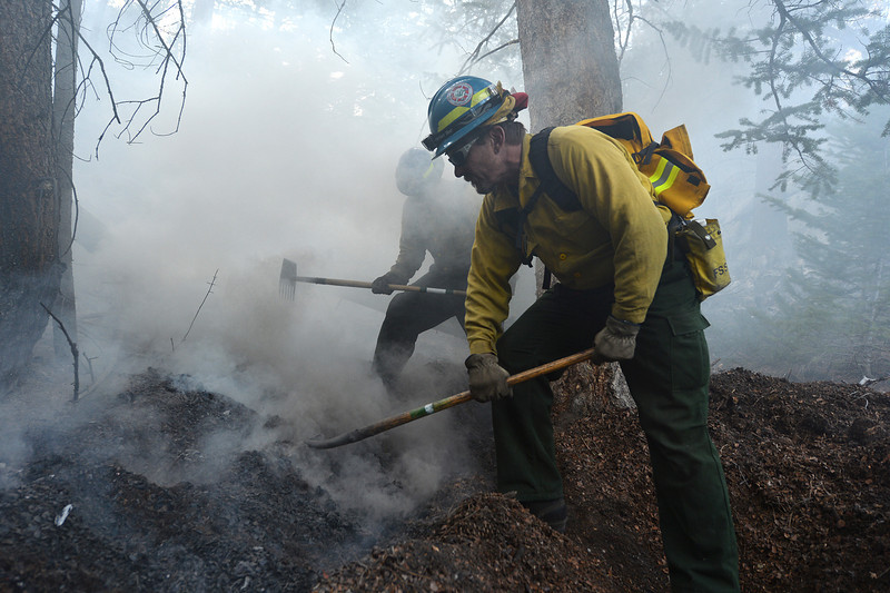 A hand crew from Boulder Mountain Fire work to snuff out a spot fire near the Cub Lake Trail on Tuesday. Crews from Alamosa, Dillon, as well as Idaho, California and WYoming joined the fight to contain the Fern Lake Fire in the national park.