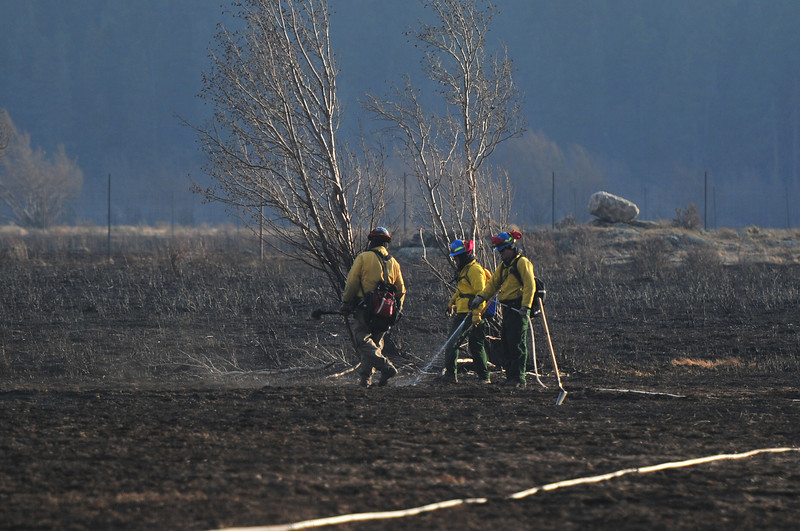 A handcrew waters ground in Moraine Park to keep spot fires under control on Tuesday. Firefighters also set backfires in order to starve the Fern Lake Fire of fuel.