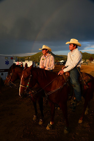 Walt Hester | Trail-Gazette<br /> Team ropers Ben McAcow of Littleton, left, and Joey Dicksen of Loveland bathe in warm sunshine as stormclowds an a rainbow pass overhead on Wednesday. The Rooftop Rodeo has offered plenty of compelling images, both inside and outside of the arena.