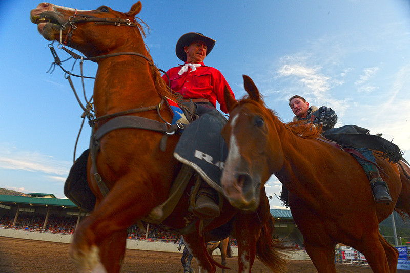 Walt Hester | Trail Gazette<br /> Pickup man Scott McLain aids a bareback rider during Friday's Rooftop Rodeo. The pickup men help riders safely get off the rough stock and help wrangle the big, afletic animals, including the bulls.