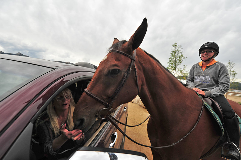 Jacqueline Kramig feeds Cue, with Samantha Kramig astride, all from Castle Rock, on Wednesday. While the horse did not compete, Cue still enjoyed a few mints.