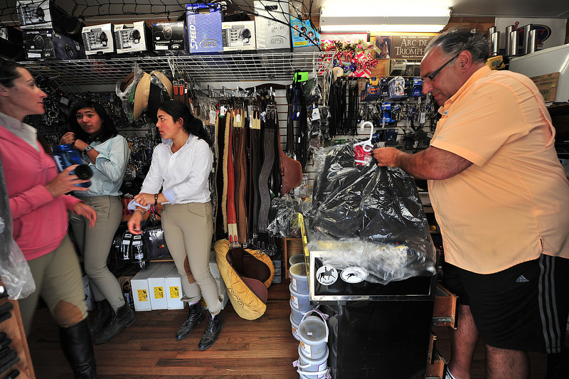 Ali Kovach, Surina Techarukpung, 15, and sister Norma, 16, purchase a few bargain items on Wednesday from  Jim Calariso of Fox Creek Mobile Equine Outfitters. Some of the vendors have discounted their wares, and some are packing up shops as the hunter-jumper festival winds down.