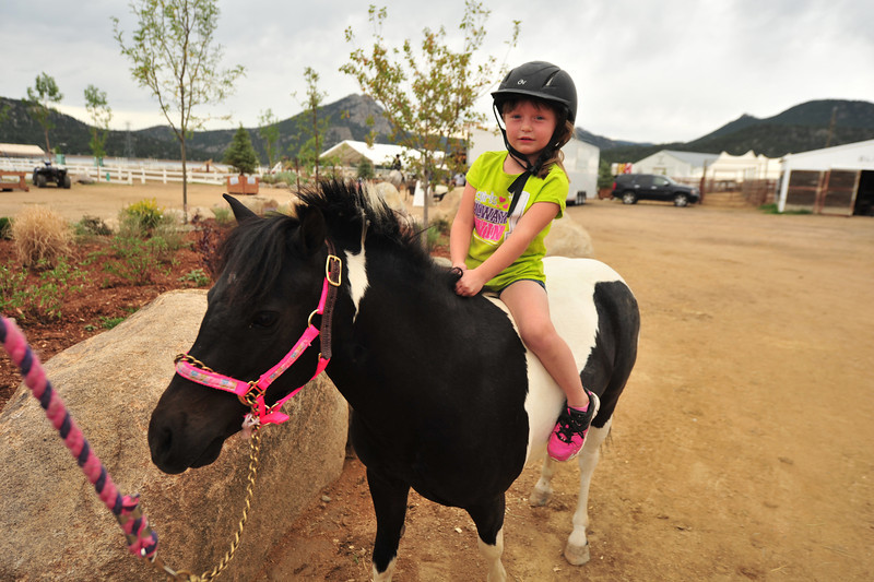 Aven Sowder, 3, of Castlerock, Colo., rides her little horse, Gumdrop, at the Stanley Fairgrounds on Wednesday. The pair were at the hunter-jumper show for fun, not as competitors, yet.