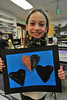 Josie Ryan, 8, proudly displays her project in class on Monday. While elementary school art teaches lines, shapes and colors, good art teachers promote creative thinking, which will help a student in many areas of life.