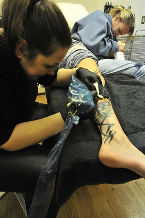 09EPLPht1 The process.jpg Artist Josalin Livingstone adds color to Renee Dehaven Willard's tattoo. Livingstone and her shop are not typical among tattoo parlors and artists.